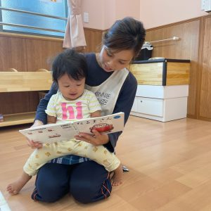 園児を膝に乗せて本を読んでいる保育士