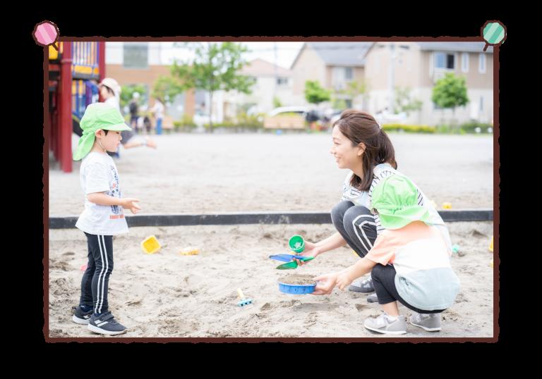 保育士と子どもたちが砂場で遊んでいる